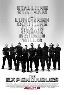 Nine armed men dressed in black standing shoulder to shoulder, Sylvester Stallone front and center